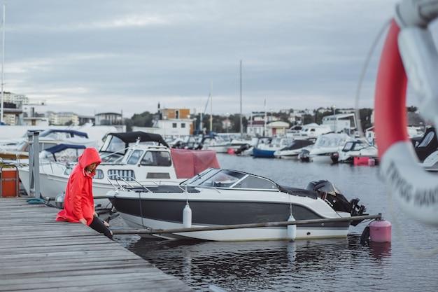 aef68618ed29e6 Bella giovane donna in un mantello rosso nel porto degli yacht ...