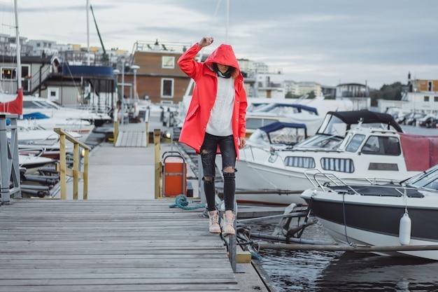 4c7ea42745874e Bella giovane donna in un mantello rosso nel porto degli yacht. stoccolma,  svezia Foto