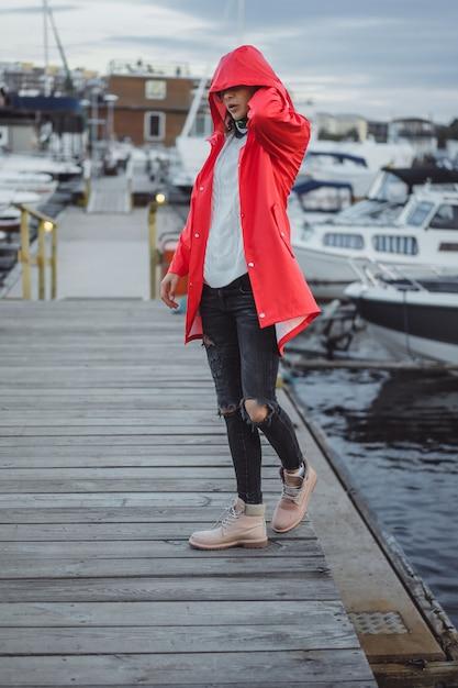 Bella giovane donna in un mantello rosso nel porto degli yacht. stoccolma, svezia Foto Gratuite