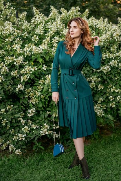 Bella giovane donna in una passeggiata in un abito verde. Foto Premium