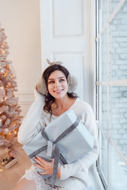 Bella giovane donna in vestito bianco che posa con il contenitore di regalo Foto Gratuite