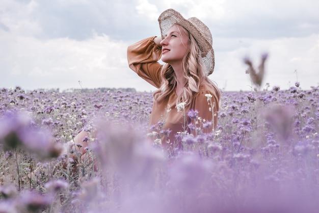 Bella giovane donna incinta in cappello in campo di lavanda. fiori che sbocciano Foto Premium