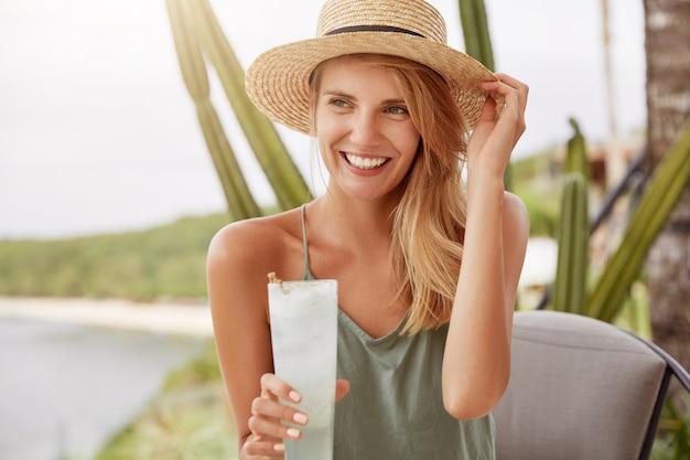 Bella giovane donna indossa cappello di paglia e maglietta casual, beve cocktail freschi, guarda con espressione sognante in lontananza. modello femminile con bevanda esotica. ricreazione femminile adorabile alla caffetteria Foto Gratuite