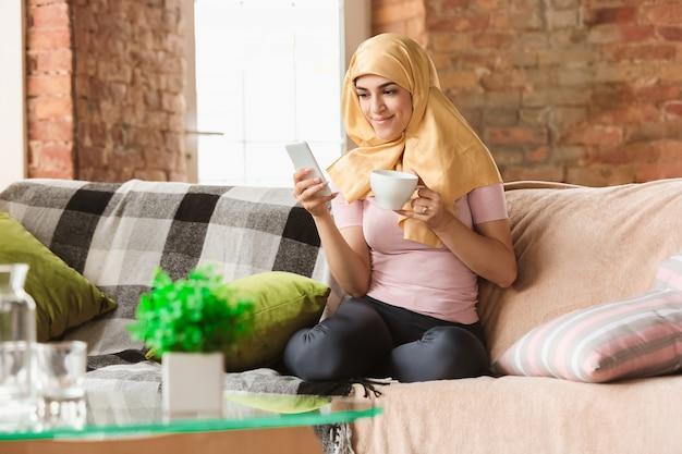 Bella giovane donna musulmana a casa durante la quarantena e l'autoisolamento, utilizzando tablet per selfie o videocall, lezioni online Foto Gratuite