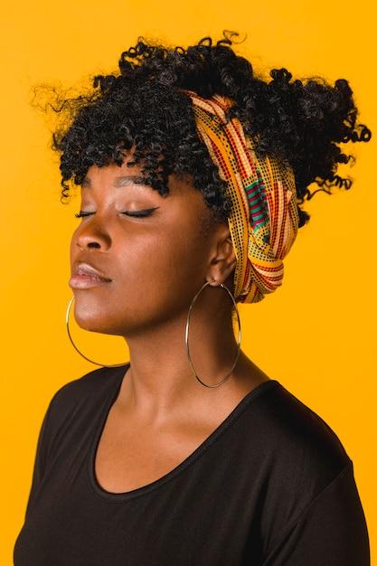 Bella giovane donna riccia africana su sfondo colorato Foto Gratuite