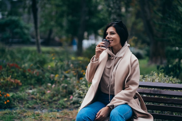Bella giovane donna seduta su una panchina a bere il caffè godendo nel parco Foto Gratuite