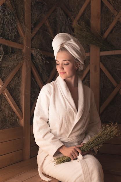 Bella giovane donna sorridente che si siede sul banco alla sauna Foto Gratuite