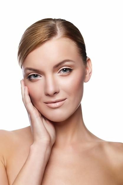 Bella giovane donna sorridente con viso sano e pelle pulita Foto Gratuite