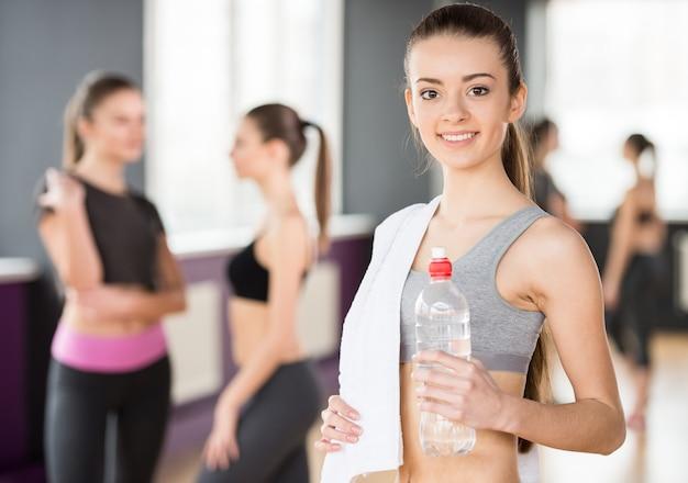 Bella giovane donna sportiva con acqua in palestra. Foto Premium