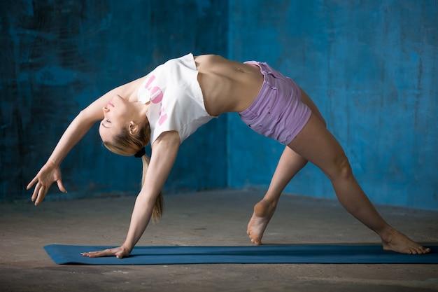 Bella giovane donna sportiva fare la postura di camatkarasana Foto Gratuite