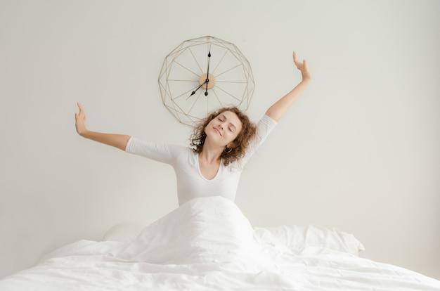 Bella giovane donna svegliarsi e stretching nel suo letto la mattina Foto Premium