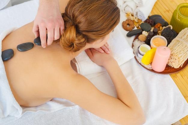 Bella, giovane e donna in buona salute nel salone della stazione termale. trattamento di massaggio Foto Premium