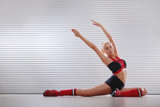 Bella giovane femmina atletica che allunga prima del suo allenamento Foto Gratuite