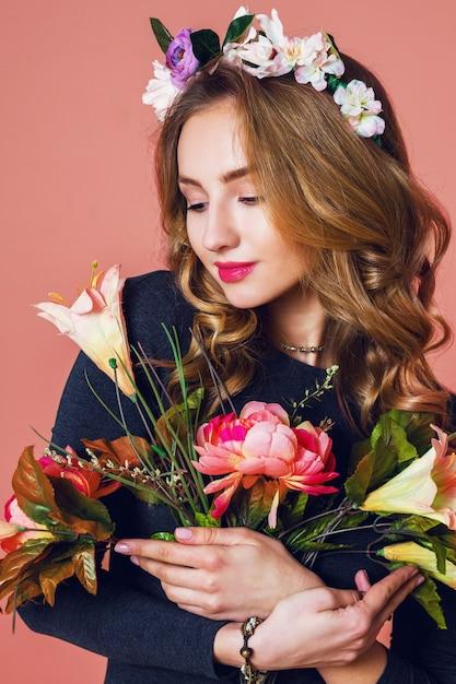 Bella giovane femmina con lunghi capelli biondi ondulati in corona di fiori primaverili in posa con bouquet di fiori su sfondo rosa. Foto Gratuite