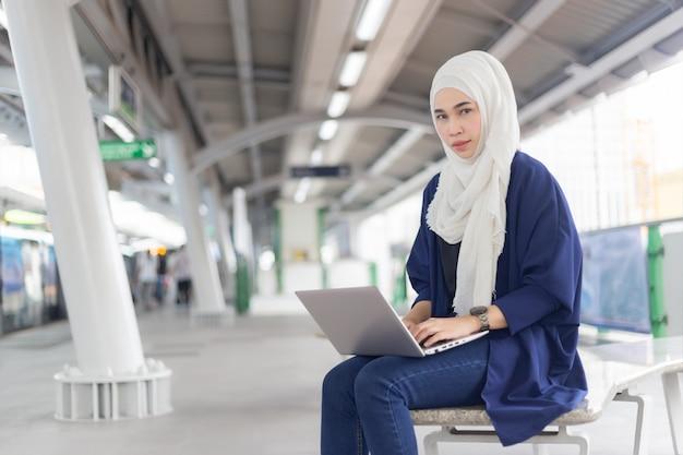 Bella giovane ragazza asiatica che lavora ad uno skytrain con un computer portatile. donne musulmane Foto Premium