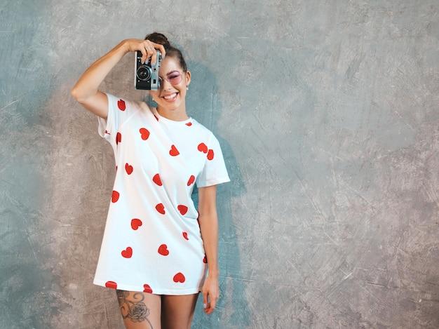 Bella giovane ragazza sorridente del fotografo che prende le foto usando la sua retro macchina fotografica. Foto Gratuite