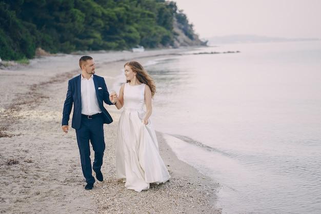 Bella giovane sposa dai capelli lunghi in abito bianco con il suo giovane marito sulla spiaggia Foto Gratuite