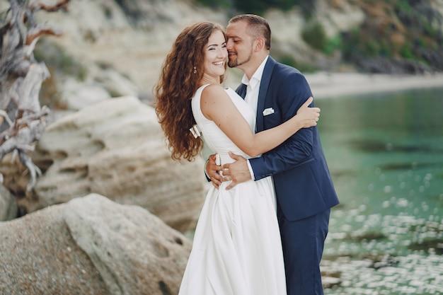 Bella giovane sposa dai capelli lunghi in abito bianco con il suo giovane marito vicino al fiume Foto Gratuite