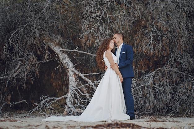 Bella giovane sposa dai capelli lunghi in abito bianco con il suo giovane marito vicino filiali Foto Gratuite