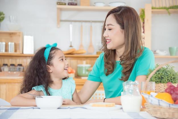 Bella madre e figlia asiatiche che mangiano prima colazione insieme a casa di mattina Foto Premium