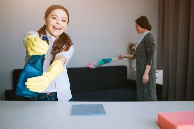 Bella madre e figlia caucasiche castane che puliscono insieme nella sala. bella ragazza divertente guarda su caera e usa psray su di esso. lei gioca. sua madre ha fatto esplodere la polvere dietro. Foto Premium