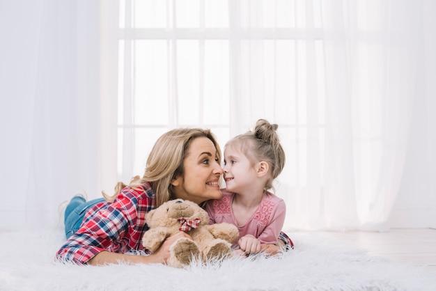 Bella madre e figlia che si trovano sulla pelliccia che fa fronte divertente con l'orsacchiotto Foto Gratuite