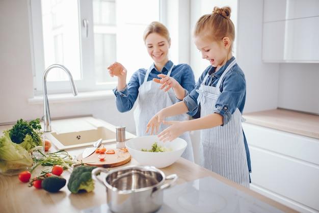 Bella madre in una camicia blu e grembiule sta preparando un'insalata di verdure fresche a casa Foto Gratuite