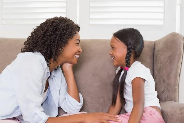 Bella madre seduta sul divano con sua figlia Foto Premium