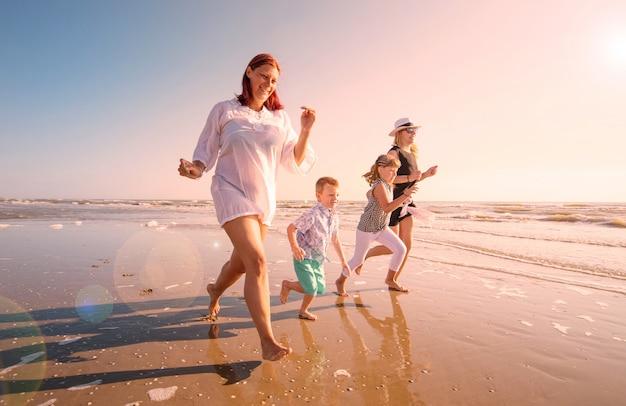 Bella mamma gioca con i suoi bambini nel mare Foto Premium