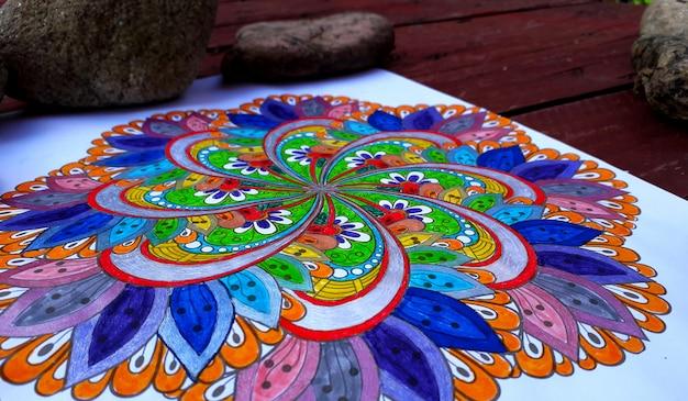Bella mandala dipinta a mano con molti colori e con alcune pietre sullo sfondo Foto Premium