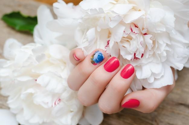 Bella mano femminile con disegno rosso dell'unghia Foto Premium