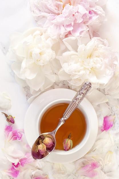 Bella natura morta con tazza di tè e peonie Foto Premium