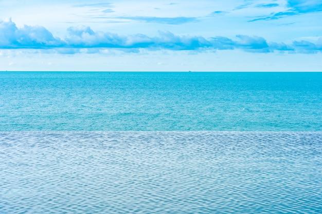 Bella piscina a sfioro all'aperto nella località di soggiorno dell'hotel con vista sull'oceano del mare e cielo blu bianco nuvola Foto Gratuite