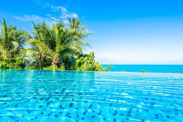 Bella piscina all'aperto di lusso nella località di soggiorno dell'hotel con l'oceano del mare intorno all'albero del cocco e nuvola bianca su cielo blu Foto Gratuite
