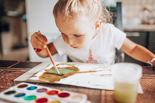 Bella pittura bionda della ragazza con il pennello e gli acquerelli nella cucina. Foto Premium