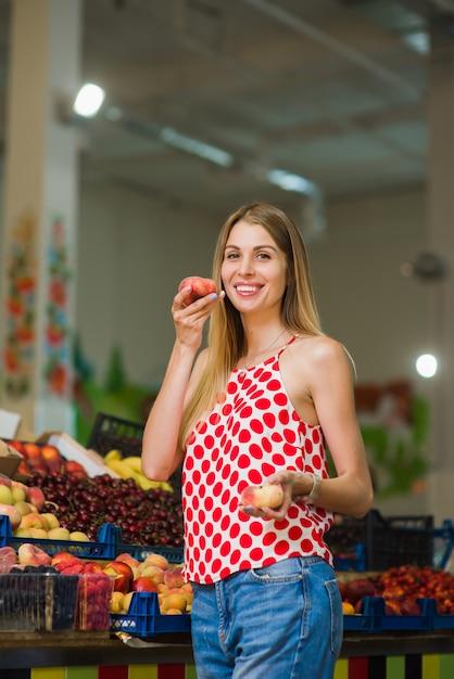 Bella posa bionda con le pesche al mercato Foto Premium