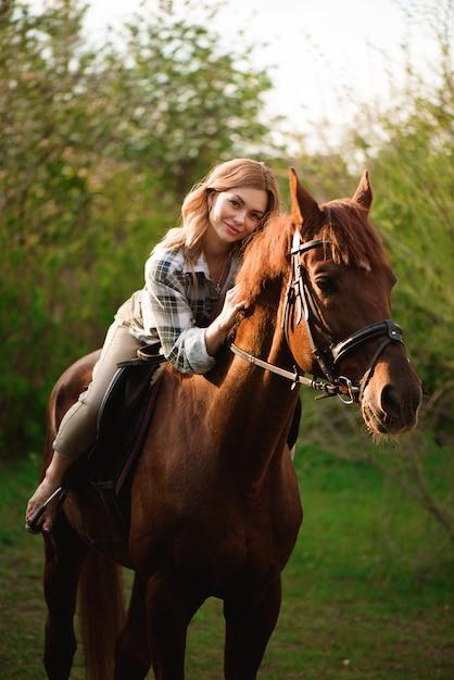 Bella ragazza a cavallo in campagna Foto Premium