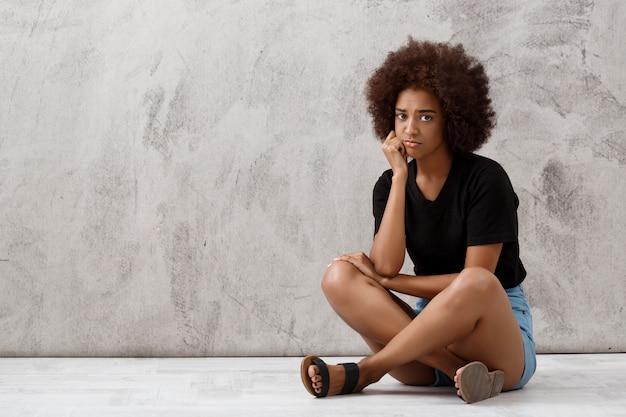 Bella ragazza africana turbata che si siede sopra la parete leggera. Foto Gratuite