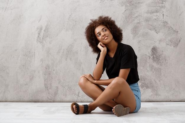 Bella ragazza africana vaga che si siede e che sorride sopra la parete leggera. Foto Gratuite