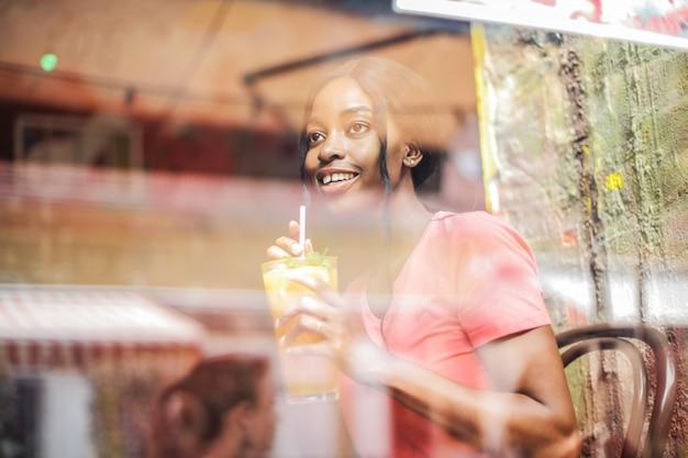 Bella ragazza afro con un coctail Foto Premium