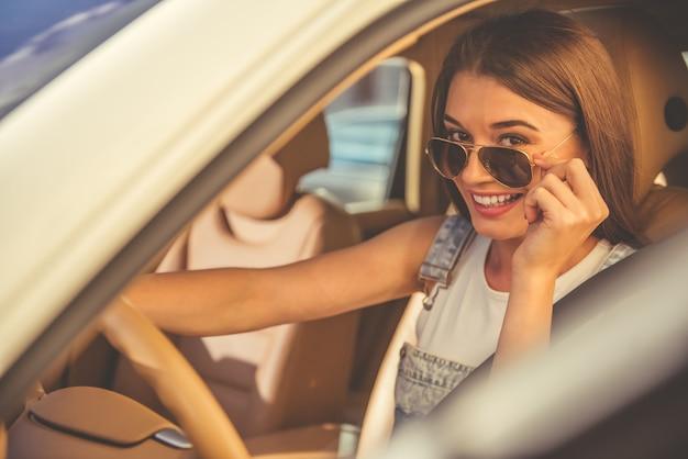 Bella ragazza alla moda in occhiali da sole alla guida di un'auto Foto Premium