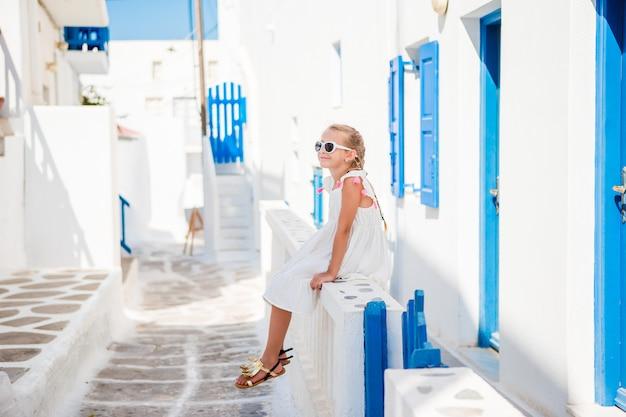 Bella ragazza alla via del tipico villaggio tradizionale greco a mykonos Foto Premium