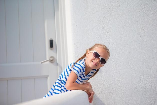 Bella ragazza alla via del tipico villaggio tradizionale greco con pareti bianche e porte sull'isola greca Foto Premium