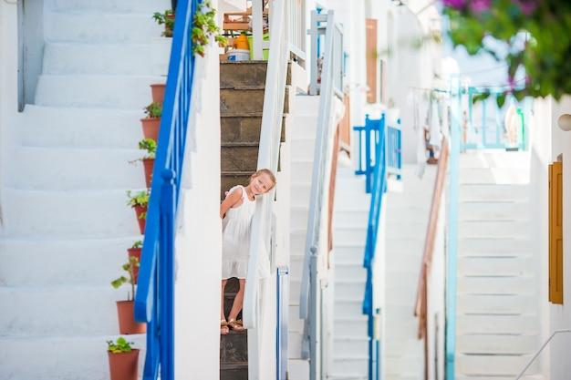 Bella ragazza alla via del villaggio tradizionale greco a mykonos Foto Premium