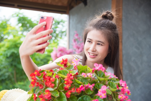 Bella ragazza asiatica che cattura la sua foto con i fiori da smart phone Foto Premium