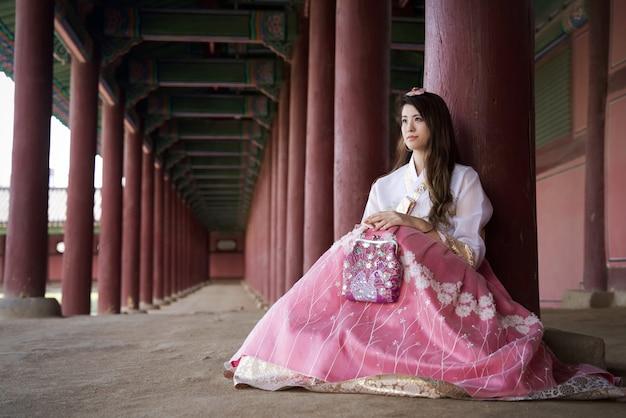 Bella ragazza asiatica con il vestito tradizionale di stile di hanbok della corea del sud che si siede con il sorriso Foto Premium