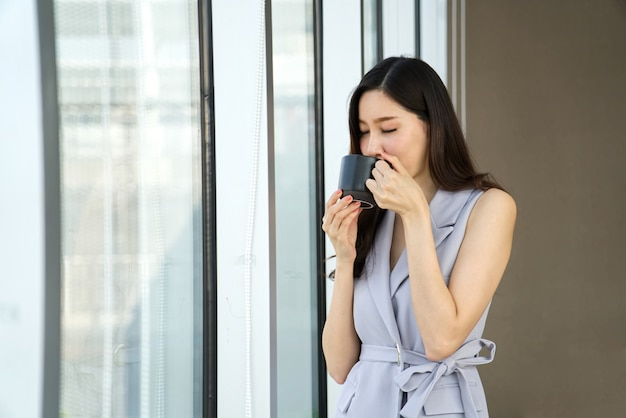 Bella ragazza astuta asiatica che parla un resto bevendo tazza di caffè che sta vicino alla finestra nell'ufficio. Foto Premium