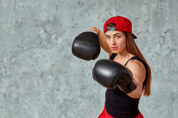 Bella ragazza atletica che posa in guantoni da pugile rosa su una parete grigia. copia spazio, primo piano. concetto di sport, lotta, raggiungimento degli obiettivi. Foto Premium