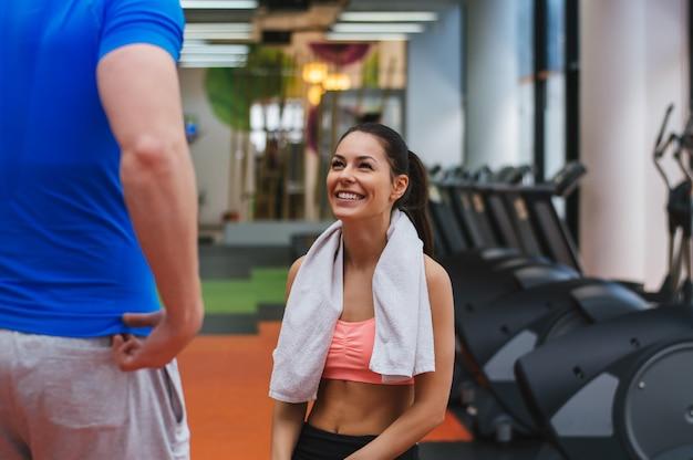 Bella ragazza avendo una consultazione con il suo personal trainer in palestra Foto Premium