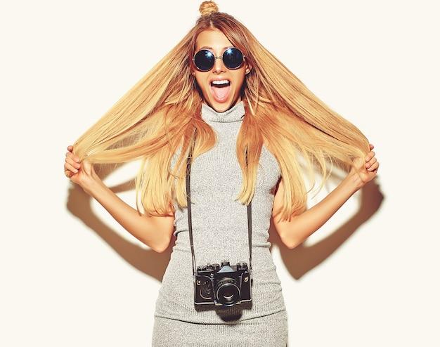 Bella ragazza bionda carina felice donna in abiti casual casual estate prende foto tenendo la macchina fotografica retrò isolata su un bianco con i capelli in mano Foto Gratuite